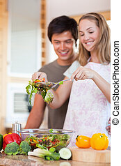 Portrait of a young couple making a salad