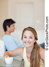 Portrait of a woman having a coffee while her husband is sitting on a sofa in their living room