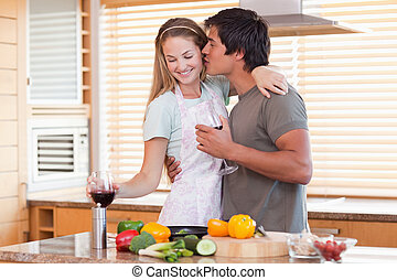 Lovely couple drinking wine while kissing in their kitchen