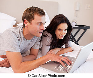 Couple using notebook together in the bedroom - Young couple...