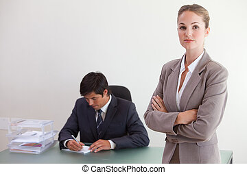 Businesswoman posing while her colleague is working in an...