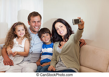 Mother taking family picture in the living room