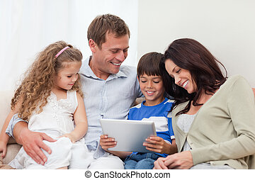 Family using tablet on the sofa - Young family using tablet...
