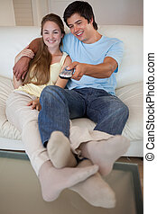 Portrait of a relaxed couple watching television