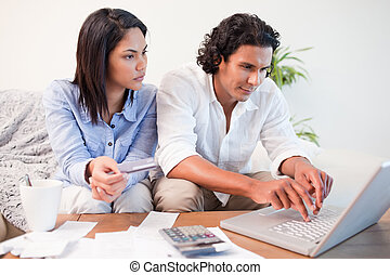 Couple checking their bank accounts online - Young couple...