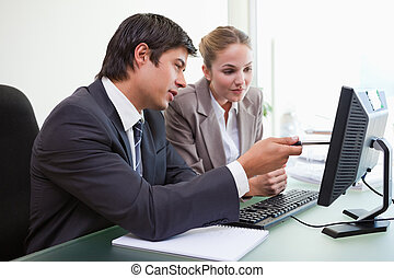 Focused business team working with a computer in an office