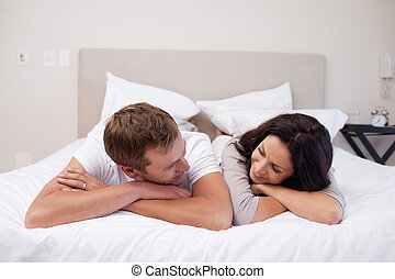 Couple laying on the bed looking at each other