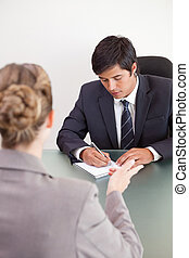 Portrait of a handsome manager interviewing a female applicant
