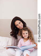 Mother and daughter reading a book on the bed