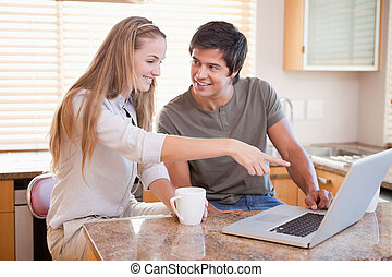 Smiling couple having coffee while using a notebook