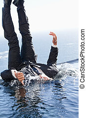 Portrait of a cheerful businessman falling into water