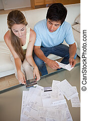 Portrait of a young couple looking at their bills in their...