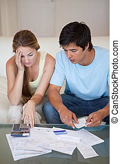 Portrait of a worried couple looking at their bills in their...