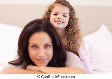 Smiling girl sitting on her mothers back