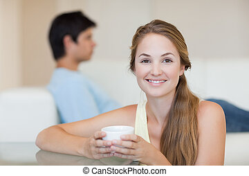 Woman drinking tea while her fiance is sitting on a couch