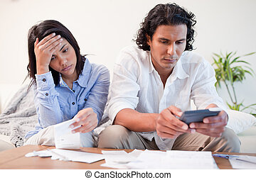 Couple checking bills - Young couple checking bills