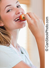 Close up of a young woman eating a strawberry