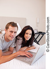 Smiling couple using laptop in the bedroom together -...