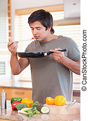 Portrait of a young man tasting his meal in his kitchen