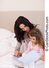 Mother reading bedtime story for her daughter - Young mother...