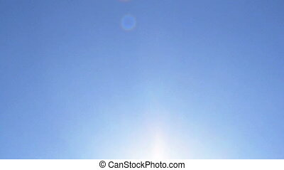 Solar and Lens flares in the sky of bright sun