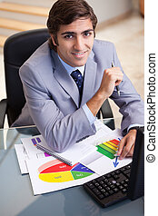 Smiling businessman working on statistics