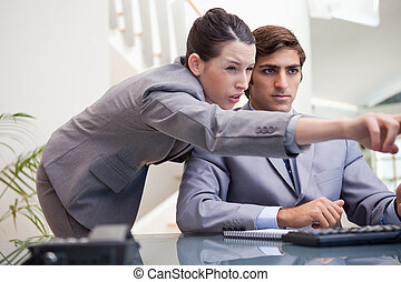 Businesswoman explaining computer program to colleague -...