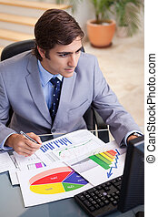 Businessman analyzing statistics at his desk - Young...