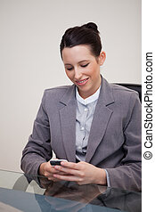 Smiling businesswoman sitting behind desk writing a textmessage