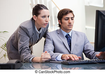 Business team looking at computer screen together - Young...