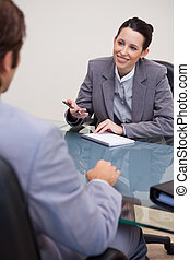 Smiling businesswoman with notepad in negotiation