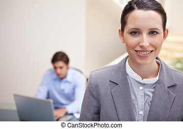 Smiling young businesswoman with colleague working on his laptop behind her