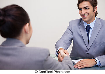 Business partners sitting at a table shaking hands - Young...