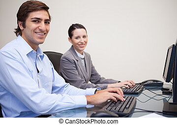 Side view of smiling colleagues working next to each other