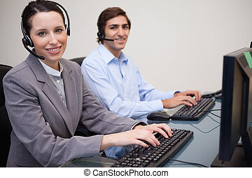 Side view of smiling call center agents at work