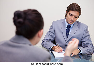 Businessman in negotiation taking notes - Young businessman...