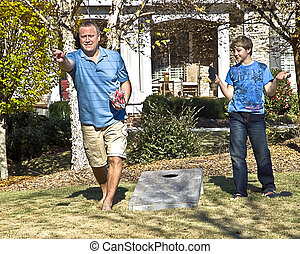 Father and Son Playing - A man and his son playing Corn Hole...