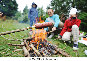 Barbecue in nature, group of people preparing sausages on fire (note: selected focus)