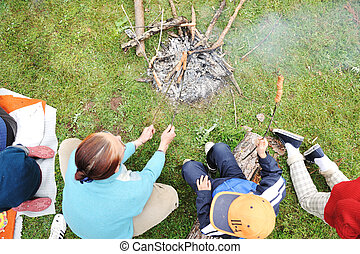 Barbecue in nature, group of people preparing sausages on...