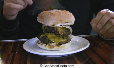 Monster Burger. - Man bites into massive two-patty hamburger...