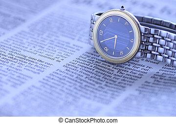 wrist  watch over newspaper