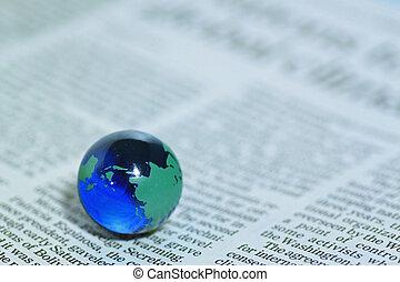 Glass globe over newspaper