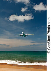 plane over a tropical beach - plane comes in to land on a...