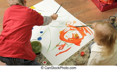 Children paint on canvas - Two small children sitting on the...