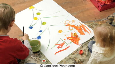 Kids paint colors - Two small children sitting on the floor...