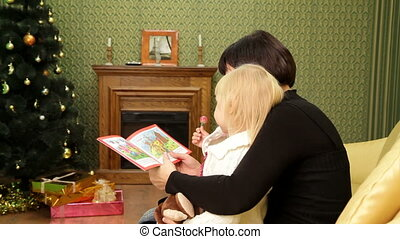 Mom reads a book her daughter - Woman reading a Christmas...