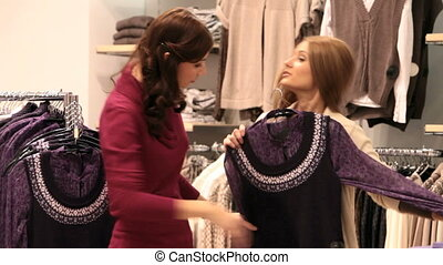 Shopping girls - Two young women looking at a pretty blouse...