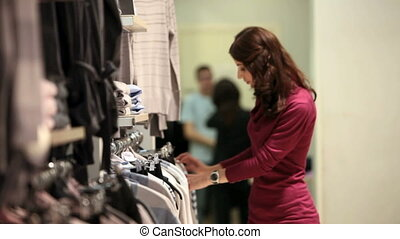 Girl in the mall - Young woman carefully picking up a shirt