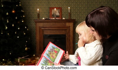 Mother and her daughter - Woman reading a Christmas story of...