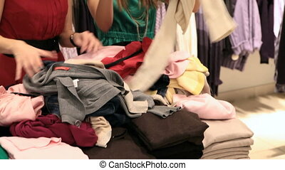 Choosing clothes out of heap - Girls choosing garments out...